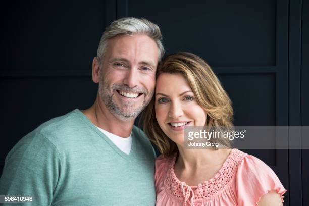 portrait of mature man and woman smiling towards camera with heads touching - 45 49 years stock pictures, royalty-free photos & images