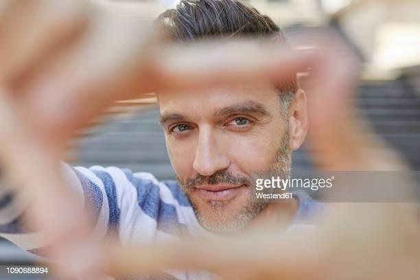 portrait of mature man building frame with his fingers - bildschärfe stock-fotos und bilder