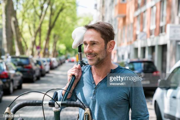Portrait of mature man carrying his bicycle on the shoulder