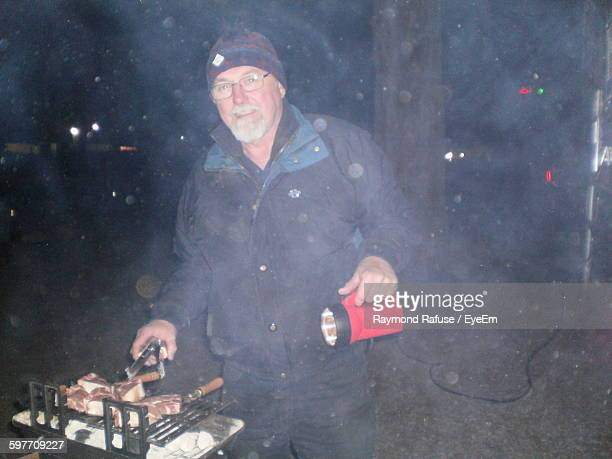 Portrait Of Mature Man Cooking Meat On Barbeque At Winter Night