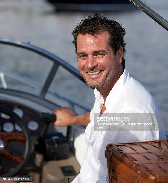 """portrait of mature man driving boat, looking over shoulder, smiling - """"compassionate eye"""" stock pictures, royalty-free photos & images"""