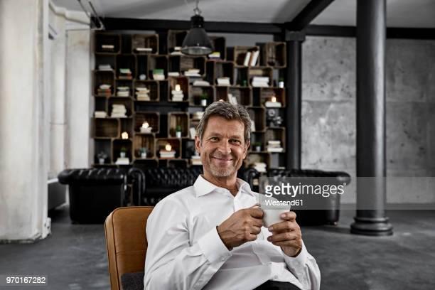 portrait of mature man enjoying cup of coffee in loft - armstoel stockfoto's en -beelden