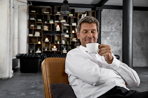 Portrait of mature man enjoying cup of coffee in loft - gettyimageskorea