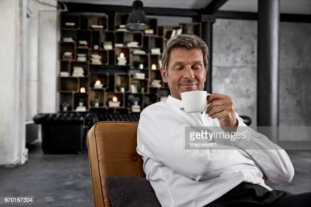 portrait of mature man enjoying cup of coffee in loft - zufriedenheit stock-fotos und bilder