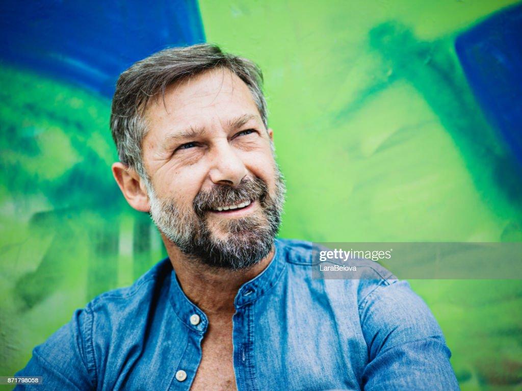 Portrait of mature man, graffiti on background : Stock Photo