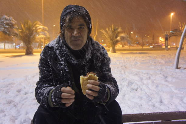 Portrait Of Mature Man Having Food While Sitting On Bench At Night