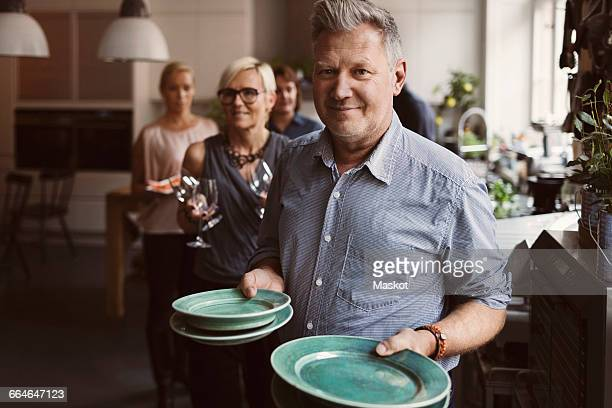 Portrait of mature man holding plates with friends in background at home