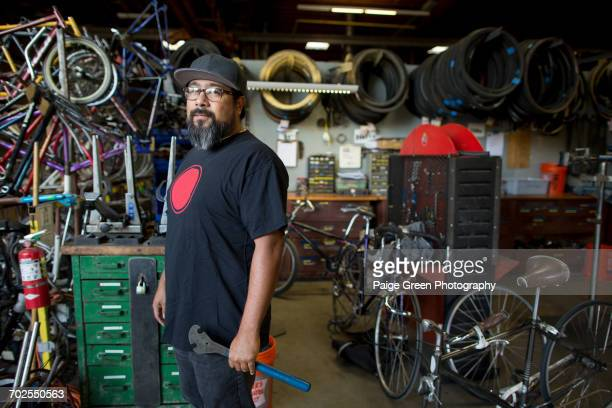 portrait of mature man holding wrench in bicycle workshop - sportgeschäft stock-fotos und bilder