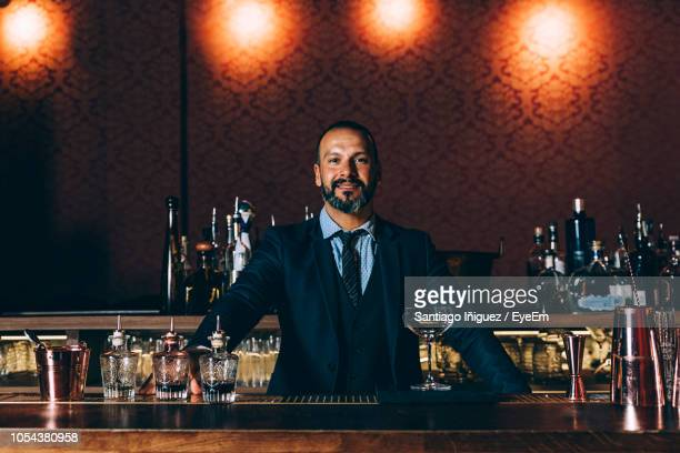 portrait of mature man in bar - bartender stock pictures, royalty-free photos & images