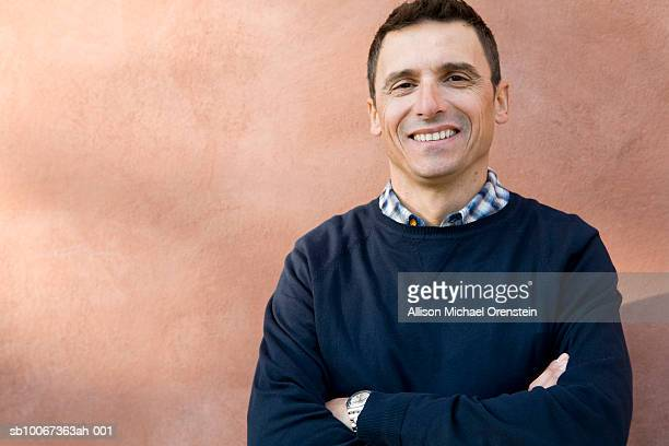 portrait of mature man in front of wall, arms crossed - italian man stock photos and pictures