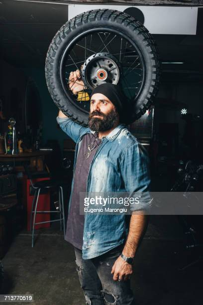 Portrait of mature man, in garage, holding motorcycle tire