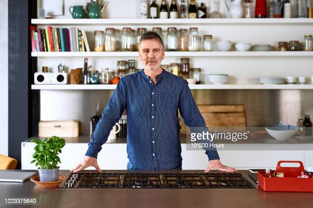 portrait of mature man in kitchen - pride stock pictures, royalty-free photos & images