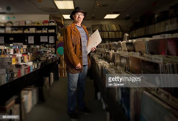 portrait of mature man in record shop, holding records - サウザンドオークス ストックフォトと画像