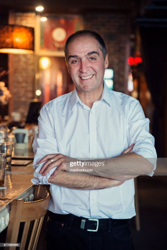 Portrait of mature man in white shirt in a bar. : Stock Photo