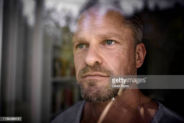 portrait of mature man looking through window - looking at view foto e immagini stock