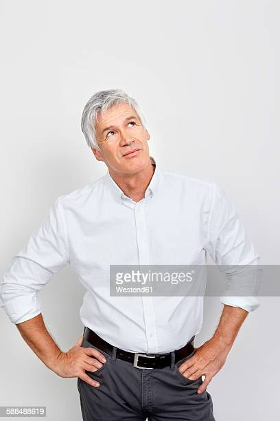 portrait of mature man looking up in thought - gesturing stock pictures, royalty-free photos & images
