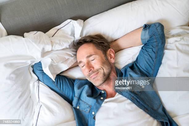 portrait of mature man lying on bed with eyes closed and hands behind head - hände hinter dem kopf stock-fotos und bilder