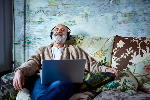 Portrait of mature man on sofa smiling and wearing headphones - gettyimageskorea