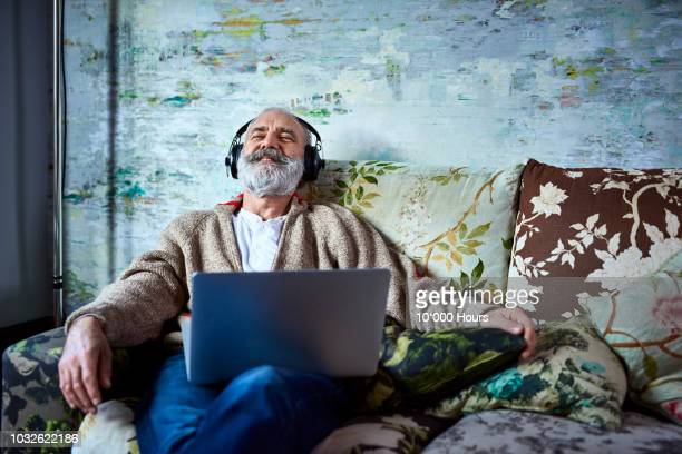 portrait of mature man on sofa smiling and wearing headphones - luisteren stockfoto's en -beelden