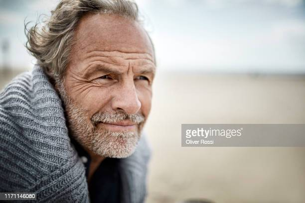 portrait of mature man on the beach - looking stock pictures, royalty-free photos & images