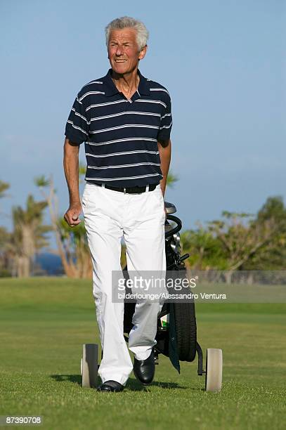 portrait of mature man pulling golf bag over golf course