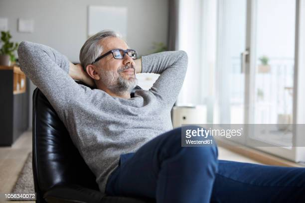 portrait of mature man relaxing at home - wohlbefinden stock-fotos und bilder