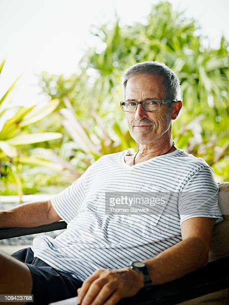 Portrait of mature man seated at tropical resort