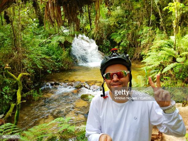 Portrait Of Mature Man Showing Peace Sign By River In Forest