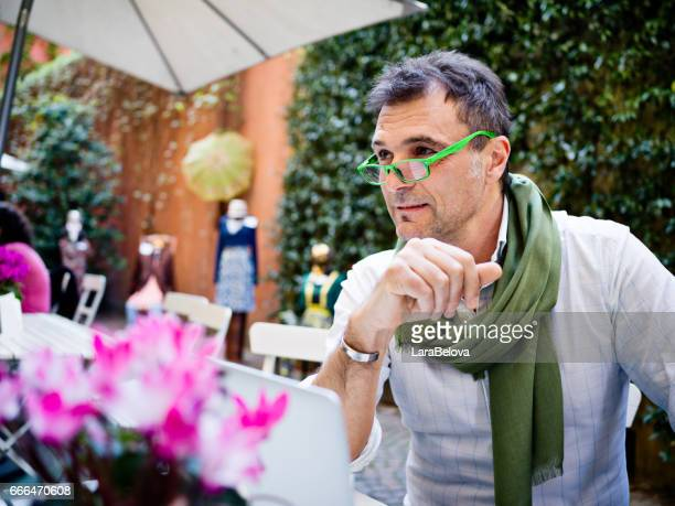 portrait of mature man  sitting at sidewalk cafe - metrosexual stock pictures, royalty-free photos & images