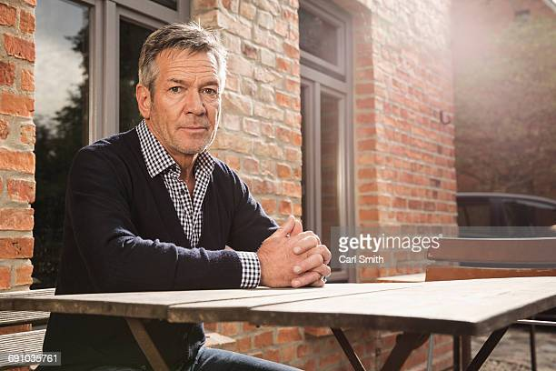 Portrait of mature man sitting at table outside house