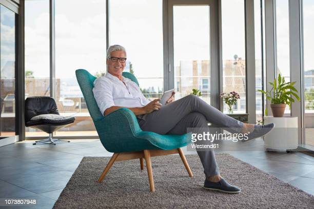 portrait of mature man sitting in armchair at home holding tablet - armchair stock pictures, royalty-free photos & images