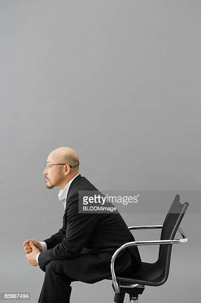 Portrait of Mature man sitting on chair, in profile, studio shot
