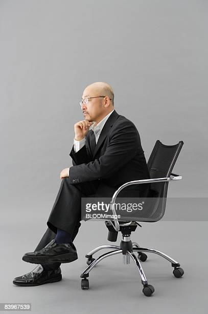portrait of mature man sitting on chair, thinking, in profile, studio shot - 足を組む ストックフォトと画像