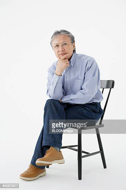 Portrait of Mature man sitting on chair with hand on chin, legs crossed, studio shot