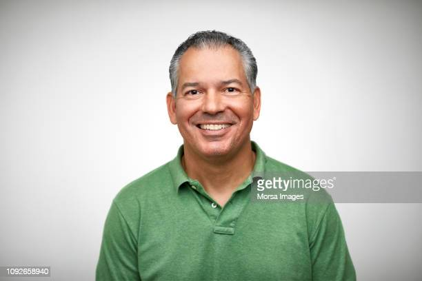 portrait of mature man smiling against white - latino américain photos et images de collection