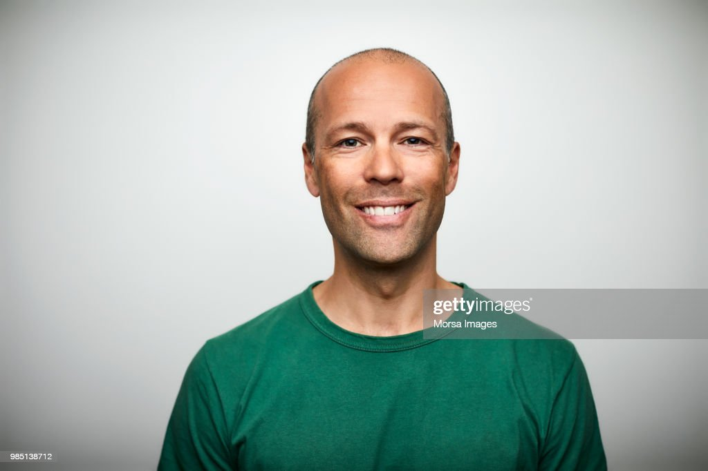 Portrait of mature man smiling on white background : Stock-Foto
