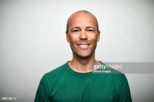 portrait of mature man smiling on white background - hoofd stockfoto's en -beelden