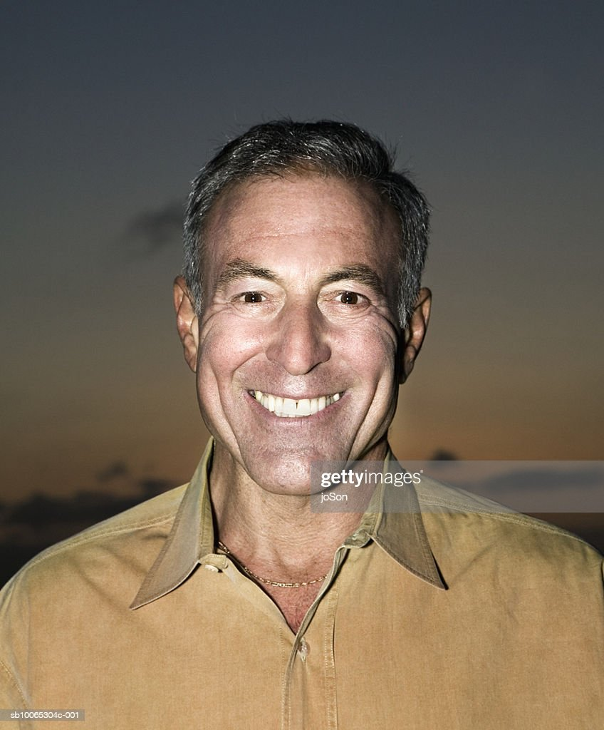 Portrait of mature man smiling, sunset sky in background : Foto stock