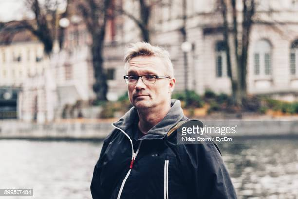 portrait of mature man standing against canal - niklas storm eyeem stock photos and pictures