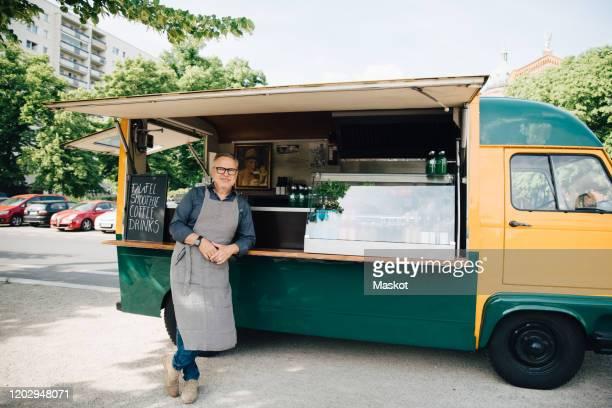 portrait of mature man standing against food truck - food truck photos et images de collection