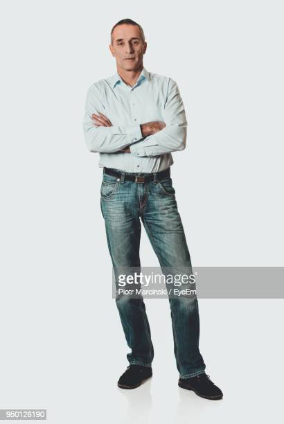 portrait of mature man standing against white background - stare in piedi foto e immagini stock