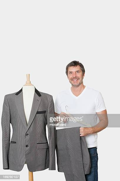 Portrait of mature man standing next to tailor's dummy over gray background