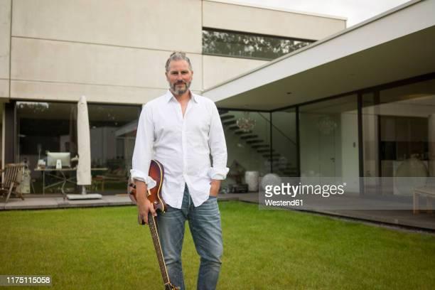 portrait of mature man standing on lawn in front of his house holding guitar - darstellender künstler stock-fotos und bilder