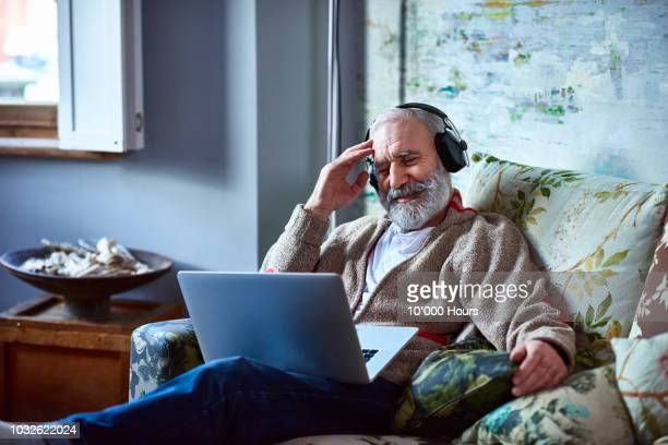 portrait of mature man streaming movie on laptop wearing headphones - mood stream stock pictures, royalty-free photos & images