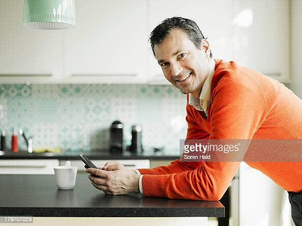 Portrait of mature man using cellphone in kitchen