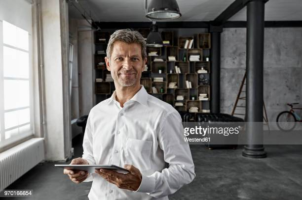 portrait of mature man using digital tablet in loft flat - waist up stock pictures, royalty-free photos & images