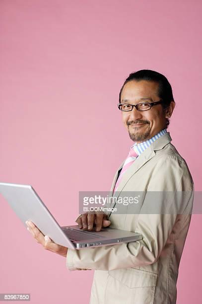 Portrait of Mature man using laptop PC, close up, studio shot