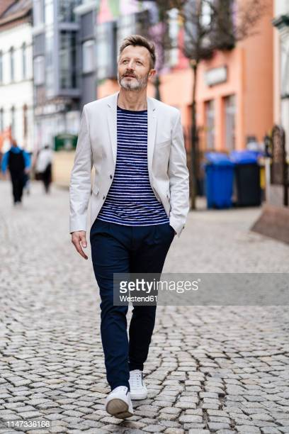 portrait of mature man walking in the city - pedestrian zone stock pictures, royalty-free photos & images