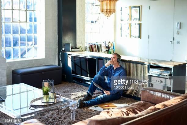 portrait of mature man wearing headphones listening to music - solo adulti foto e immagini stock