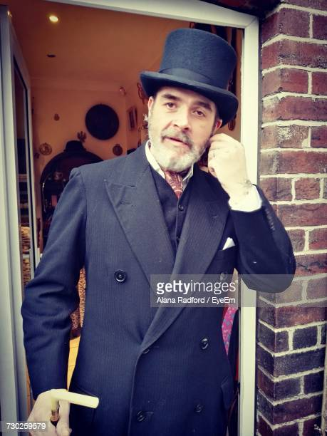 portrait of mature man wearing long coat while standing at doorway - top hat stock pictures, royalty-free photos & images